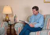 Middle-aged man relaxes on sofa in moder — Stock Photo