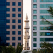 Minaret peeping between office buildings — Stock Photo