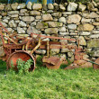 Royalty-Free Stock Photo: Old rusty plow in shadow of stone wall