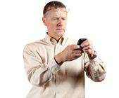 Middle aged man squinting at smart phone — Stock Photo