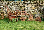 Old rusty plow in shadow of stone wall — Stock Photo