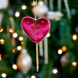 Red velvet heart in front of xmas tree — Stock Photo