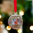 Glass ornament in front of Christmas tre — Stock fotografie