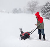 Man using snow blower on snowy drive — Stock Photo