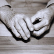 Stock Photo: Hands of old person on table