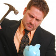 Business man with a hammer and piggy ban — Stock Photo