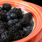 Berries and orange bowl — Stock Photo