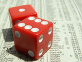 Red dice on stock report — Stock Photo