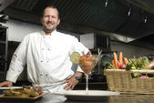Smiling chef with vegetables and shrimp — Стоковое фото