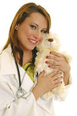 Attractive Caucasian female doctor holding stuffed animal. — Stock Photo