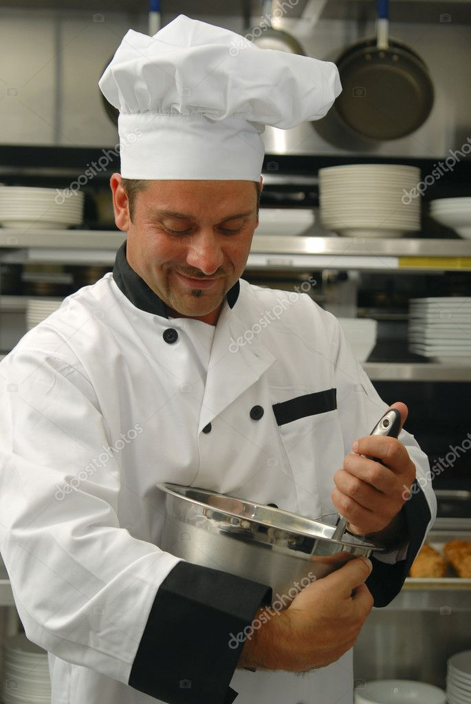 Attractive Caucasian chef mixing food in a bowl in a restaurant kitchen. — Stock Photo #1027138