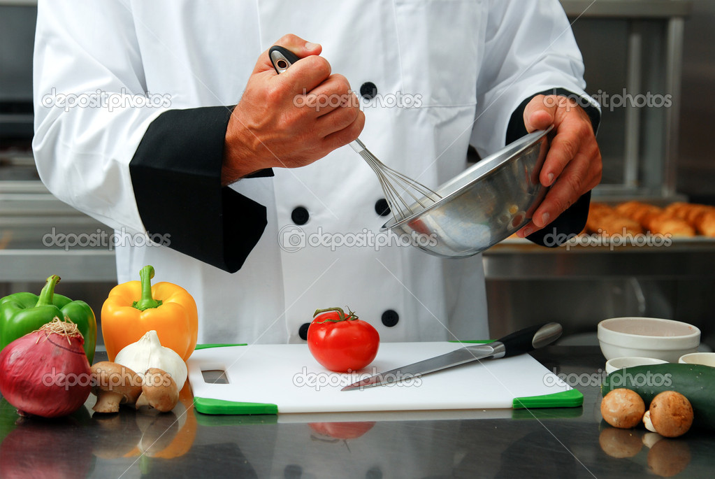 Caucasian chef mixing something in a bowl with fresh vegetables on a cutting board in front of him in a restaurant kitchen. — Stok fotoğraf #1027168