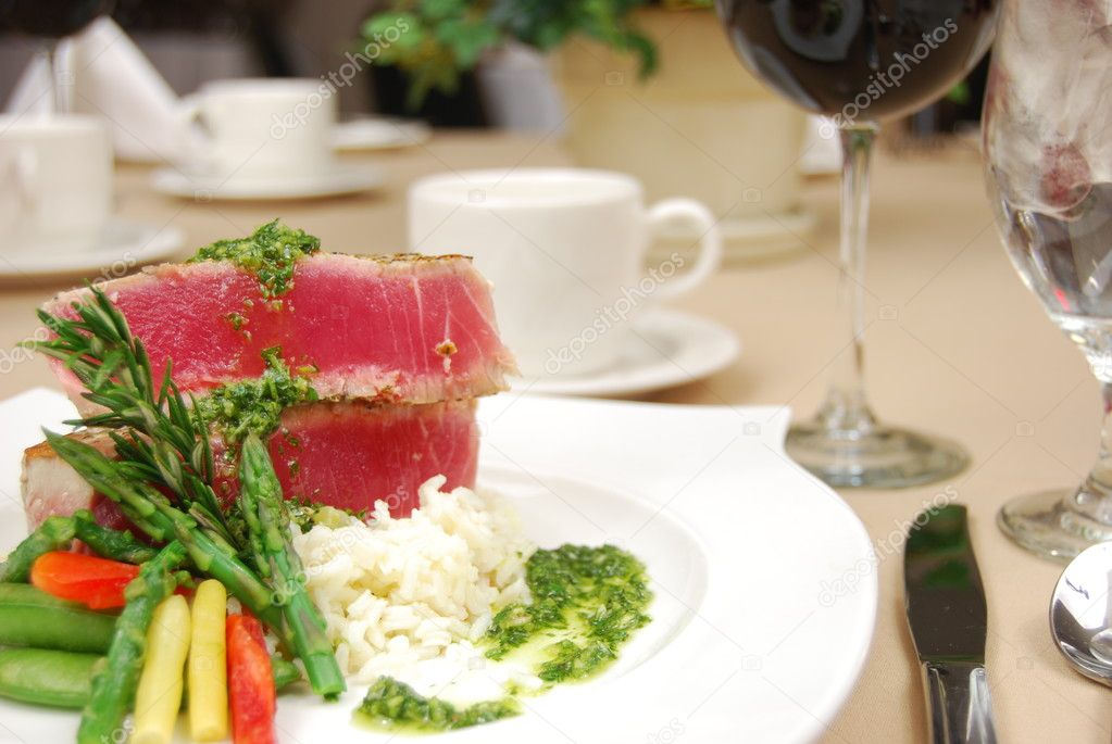 Tuna steak on a white plate isolated on a restaurant table. — Stock Photo #1029545