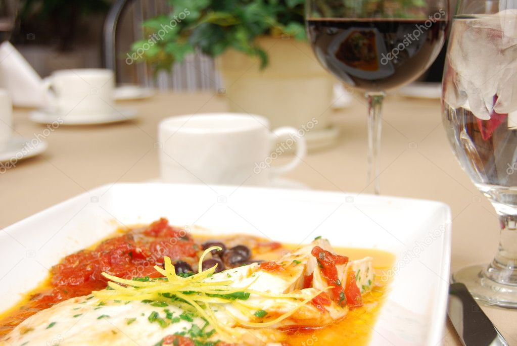 Haddock in a red sauce on a white plate on a restaurant table. — Stock Photo #1029564
