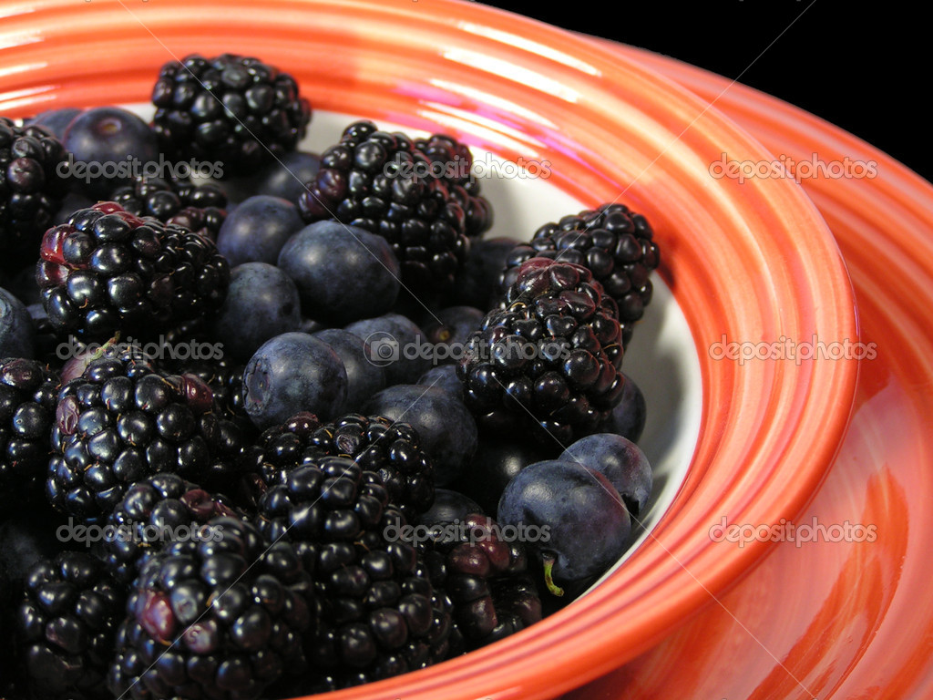Mixed blueberries and blackberries in a bowl on a plate on a black placemat — Stock Photo #1029954