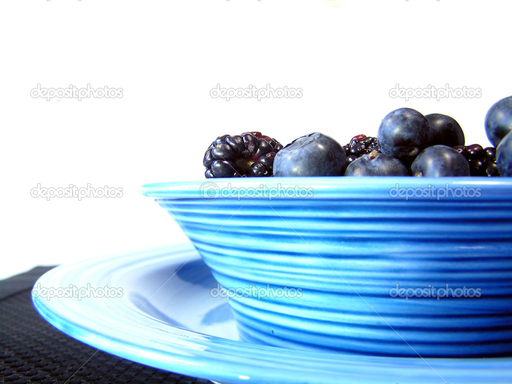 Mixed blueberries and blackberries in a bowl on a plate on a black placemat — Stock Photo #1029964