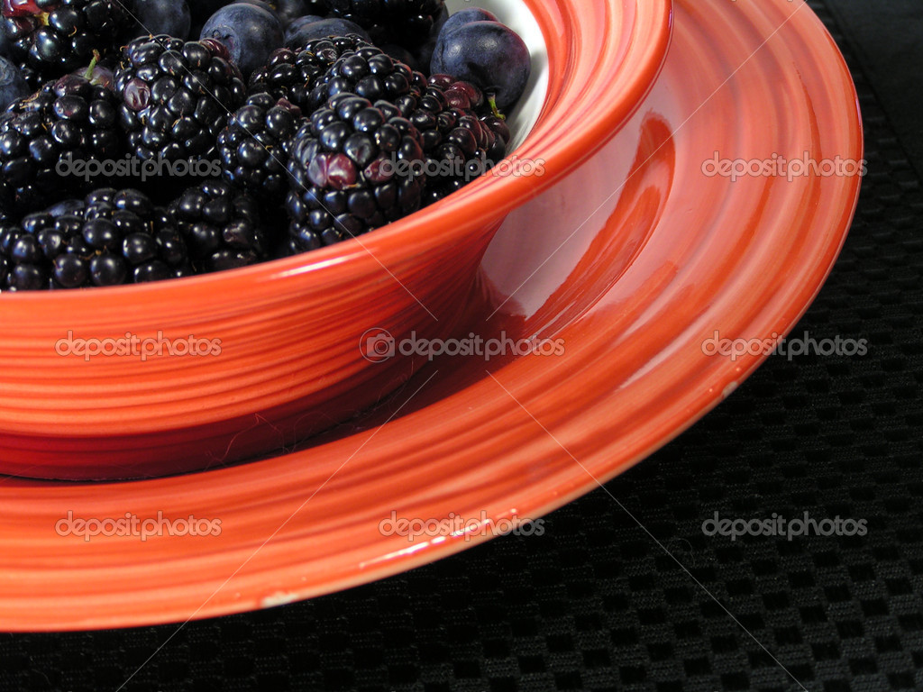 Mixed blueberries and blackberries in a bowl on a plate on a black placemat — Stock Photo #1029979