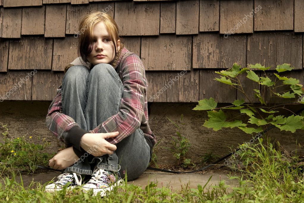A teenage girl with a sad expression sits against a run-down house.