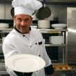 Smiling chef with empty plate - Stock Photo