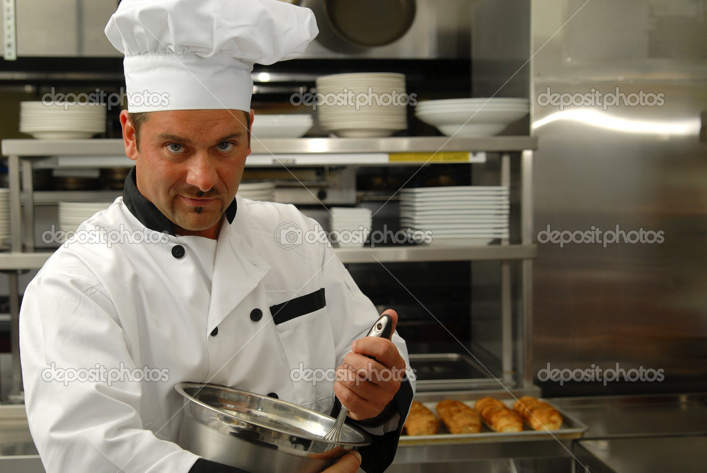 Attractive Caucasian chef mixing food in a bowl in a restaurant kitchen.  Photo #1183927