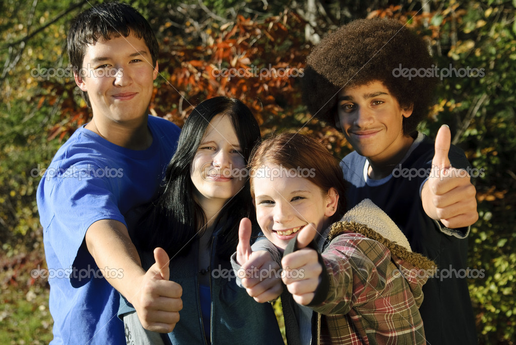 Teens of various ethnic backgrounds outdoors giving a thumbs up. Focus on teen girl second from right. — Stock Photo #1183985