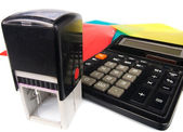 Modern rubber stamp and calculator — Stock Photo