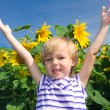 Stock Photo: Little girl and sunflowers