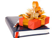 Red gift and notebook with pen — Stock Photo