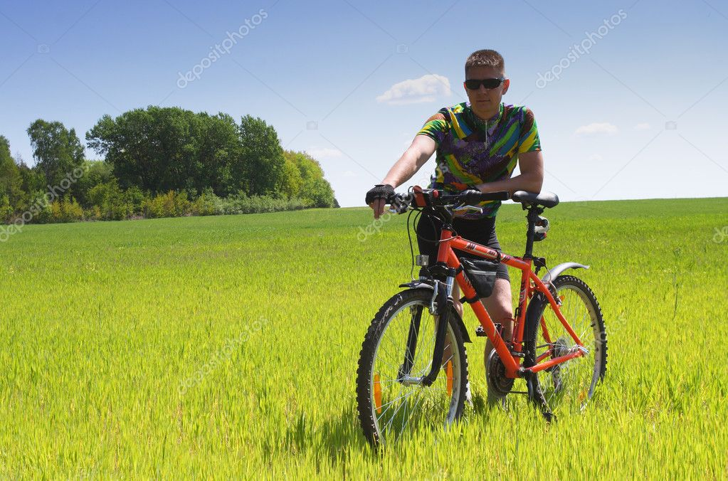 Young Biker tourist relaxation in green field — Stock Photo #2568832