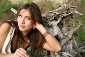 Girl near a tree root — Stock Photo
