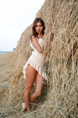 Pretty girl near haystack — Stock Photo