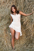 Pretty girl near haystack — Stock Photo