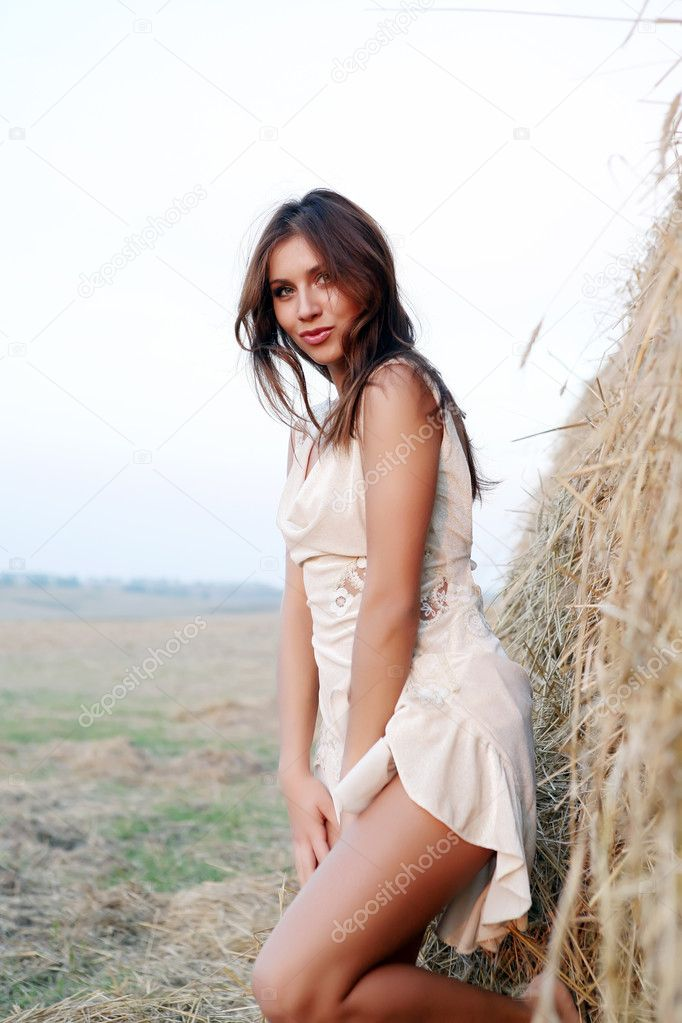 The young sexual girl stand near haycock. — Stock Photo #1060094