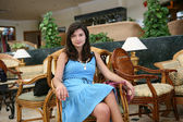 Pretty young woman sits on the armchair. — Stock Photo