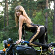 Young women with black motorcycle. — Stock Photo