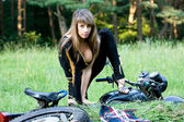 Young women with black motorcycle. — Stockfoto