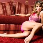 Pretty female model near the red sofa. — Stock Photo