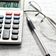 Pen, calculator and glasses — Stock Photo