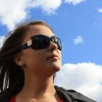 Симпатичная девушка против голубого неба. — Стоковое фото