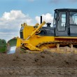 Bulldozer in fields over blue cloudy sky — Stock Photo