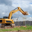 Excavator against microdistrict under co — Stock Photo