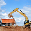 Excavator and rear-end tipper — Stock Photo