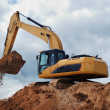 Excavator with earth in the bucket - Stock Photo