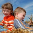 Two smiling children in straw outdoors — ストック写真