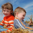 Two smiling children in straw outdoors — Stok fotoğraf