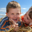 Smiling boy and girl in straw outdoors c — Stock Photo