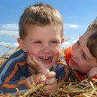 Stock Photo: Smiling boy and girl in straw outdoors c
