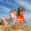 Smiling boy and girl in straw outdoors — Stock Photo