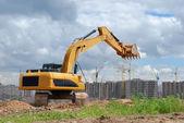 Excavator against microdistrict under co — Stock Photo