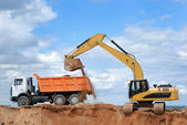 Excavator and rear-end tipper — Stockfoto